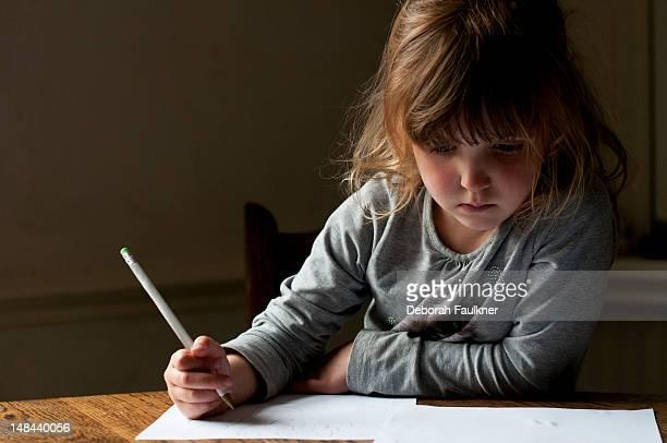 small girl writing - ein mädchen allein stock-fotos und bilder