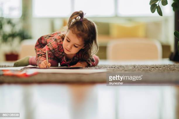 small girl writing with felt tip pen while relaxing on carpet at home. - colouring stock pictures, royalty-free photos & images