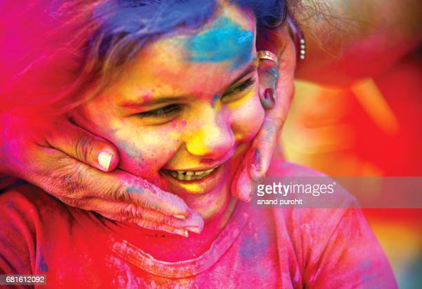 A small girl's face is being smeared with colors during the Hindu festival of Holi, India