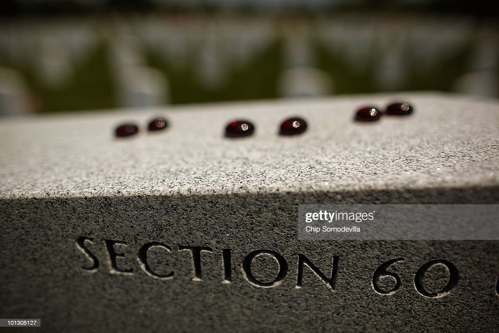 Small glass stones are placed on top of a headstone on Memorial Day in Section 60 of Arlington National Cemetery May 31, 2010 in Arlington, Virginia. Section 60 is where troopers killed in Iraq and Afghanistan are buried. This is the 142nd Memorial Day observance at the cemetery.