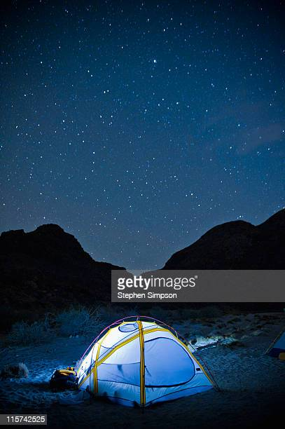 small glowing tent and desert night sky
