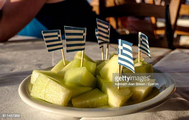 small greek flags stuck in fruit slices on plate - greek flag stock pictures, royalty-free photos & images