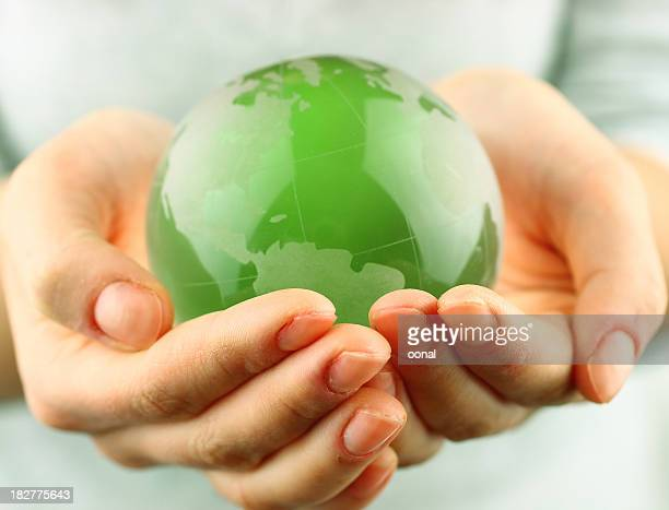 Small green globe in two cupped hands