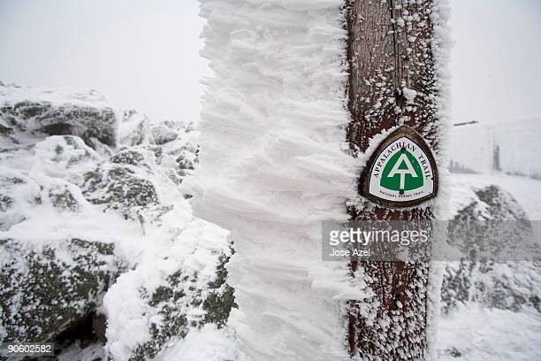 A small, green snow covered sign points to the Appalachian Trail  in the White Mountains of New Hamp