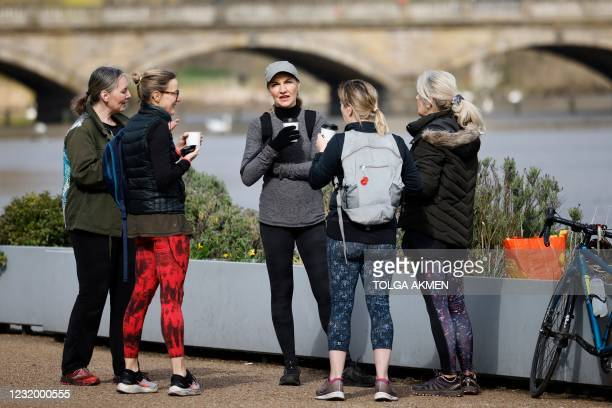 Small group chat over cups of coffee in Hyde Park in London on March 29 as England's third Covid-19 lockdown restrictions ease, allowing groups of up...