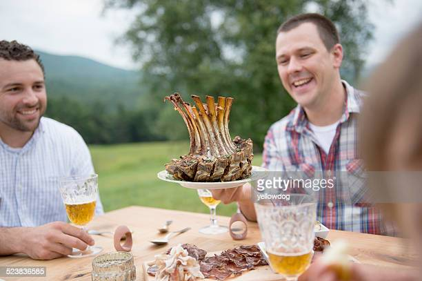 Small group of adults enjoying meal, outdoors