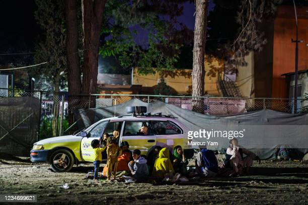 Small group of Afghans eat their meal quietly outside of their vehicle which they also use to live in temporarily, in the corner of a parking area...