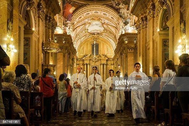 Small group of altar boys carrying a cross and censers touring the church inside the Cathedral of Cordoba Argentina on the night of Easter Thursday...