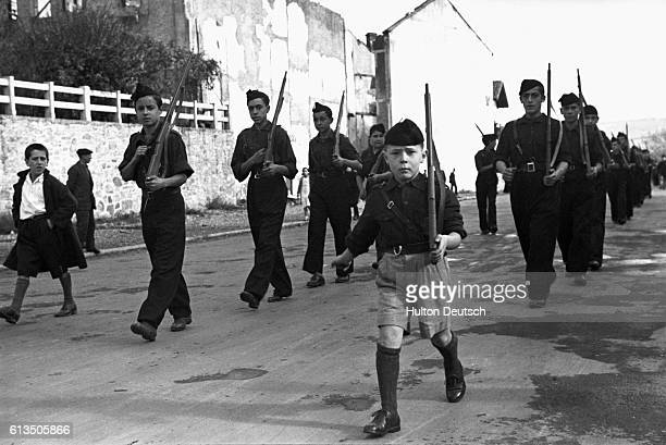A small group of armed fascist youth parades down a street in Irun Spain in November 1936 during the Spanish civil war