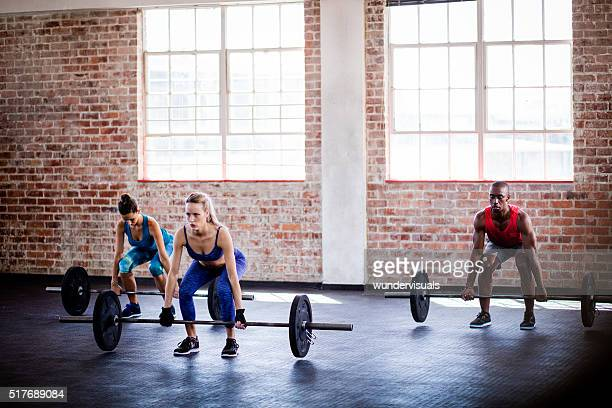Small group of athletes on weights training class at gym