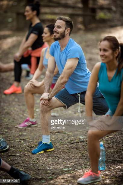kleine gruppe von athleten aufwärmen vor sport-training in der natur. - aufwärmen stock-fotos und bilder
