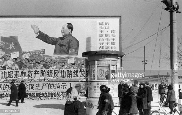 A small group of Beijing residents walk in February 1967 in downtown Beijing past a huge poster showing the Chairman Mao Zedong during the Great...