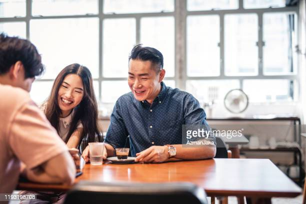 small group of chinese friends talking and drinking coffee at a cafe - caffè bevanda foto e immagini stock