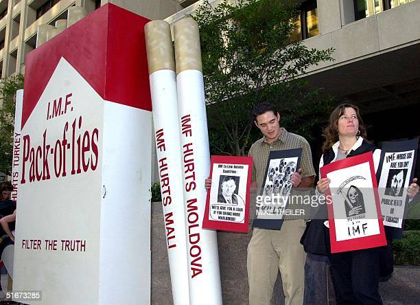 A small group of demonstrators from Essential Action sets up an oversized package of cigarettes in front of the International Monetary Fund 23...