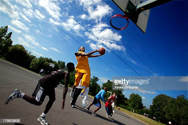 A small group of friends is playing basketball together outdoors low angle view on June 11 2005 in Sarcelles a Paris suburb France