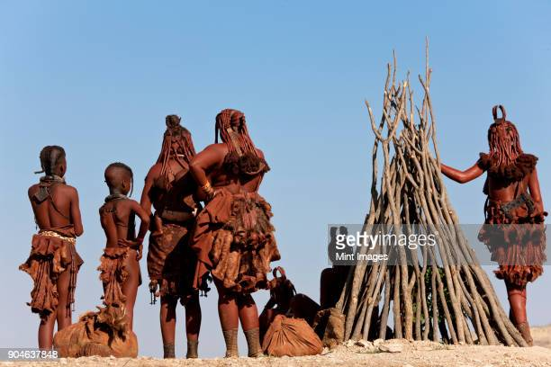 small group of himba women and children wearing traditional clothing standing in a desert. - himba stock-fotos und bilder