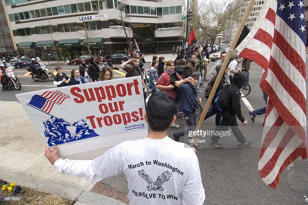 A small group of Iraq War protesters pass by a counter protester at the corner of 14th and L Streets NW on Wednesday afternoon, March, 19, 2008, the fifth anniversary of the start of the war.