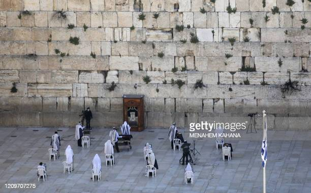 A small group of Jewish priests wearing Talit prayer shawls take part in the Cohanim prayer during the Passover holiday at the Western Wall in the...