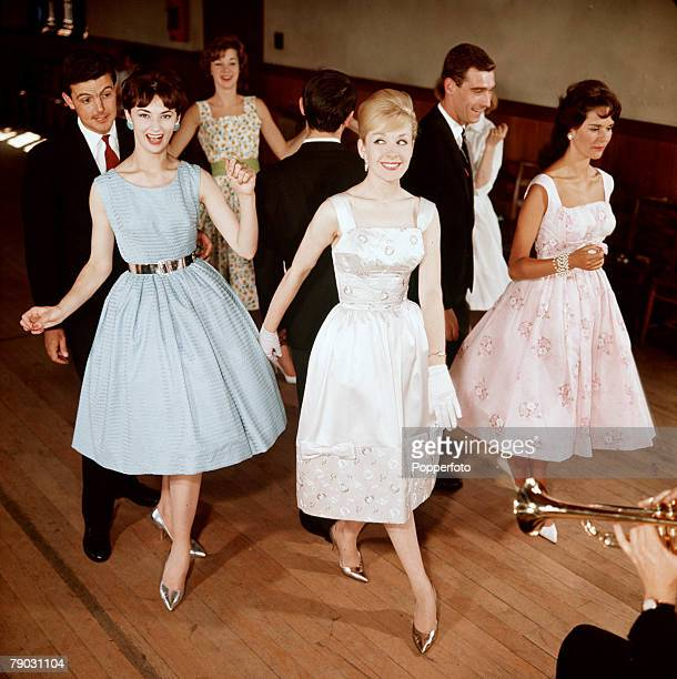 A small group of men and women dance to the music of a live band while wearing the latest fashions 1960 Men wear smart suits and ties while the women...