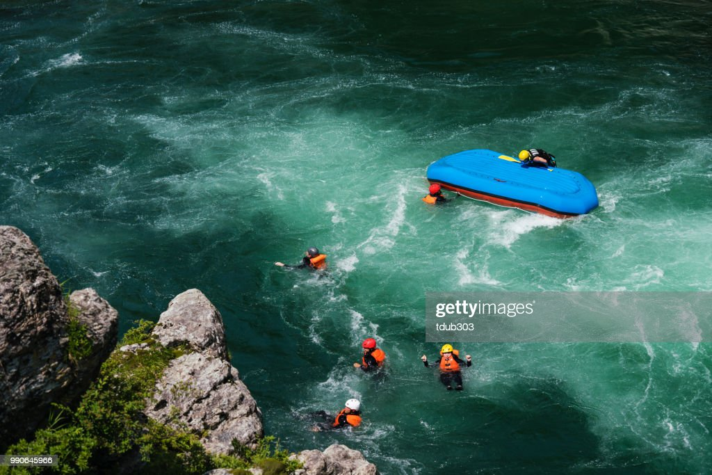 Small group of men and women floating in a river after their raft flipped over : Stock Photo