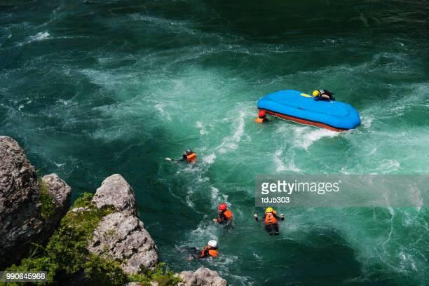 Kleine Gruppe von Männern und Frauen nach ihrem Floß umgedreht in einem Fluss schwimmende