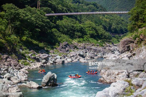 Small group of men and women in multiple boats white water river rafting