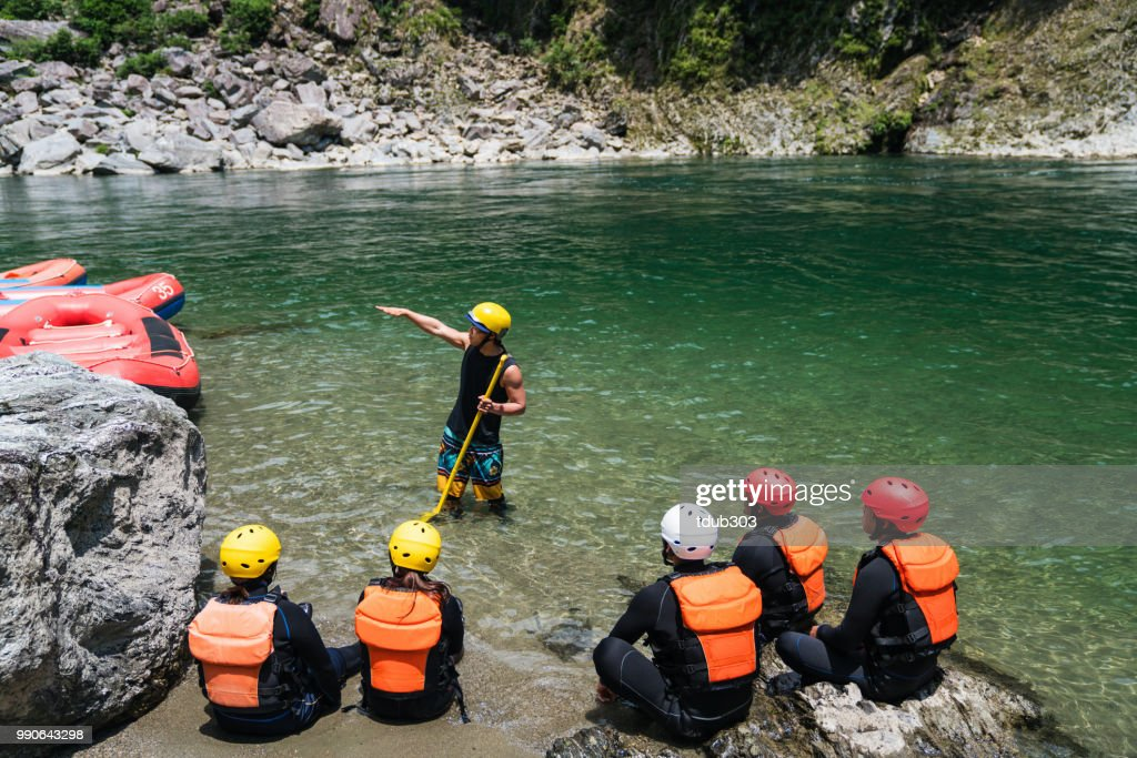 Small group of men and women preparing to go white water river rafting : Stock Photo
