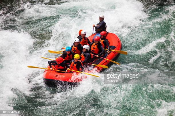 Small group of men and women white water river rafting