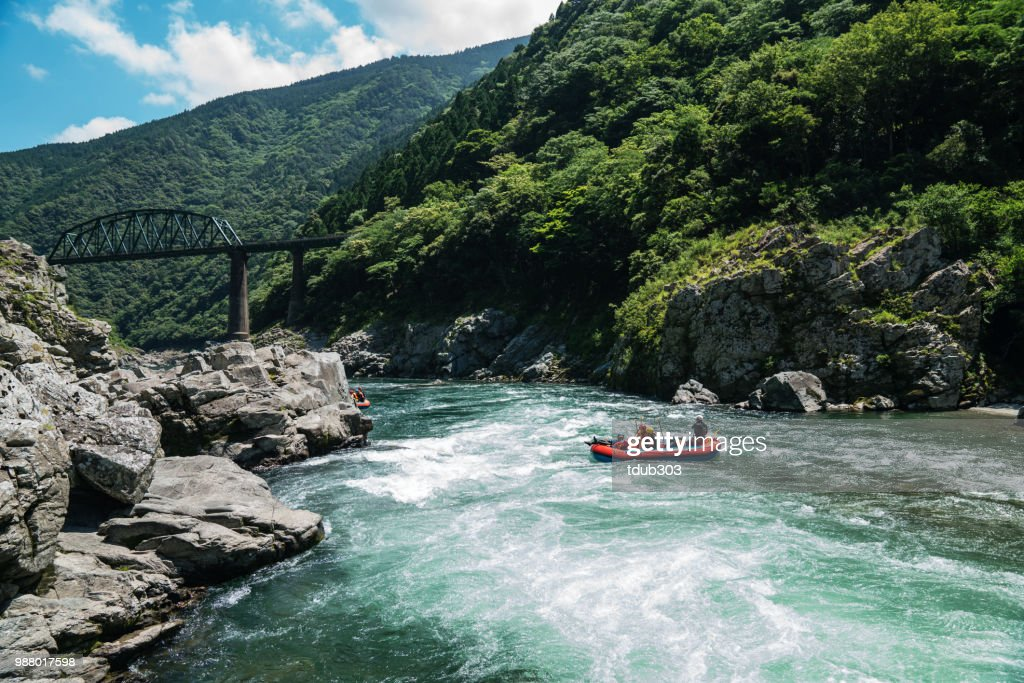 Small group of men and women white water river rafting : Stock Photo