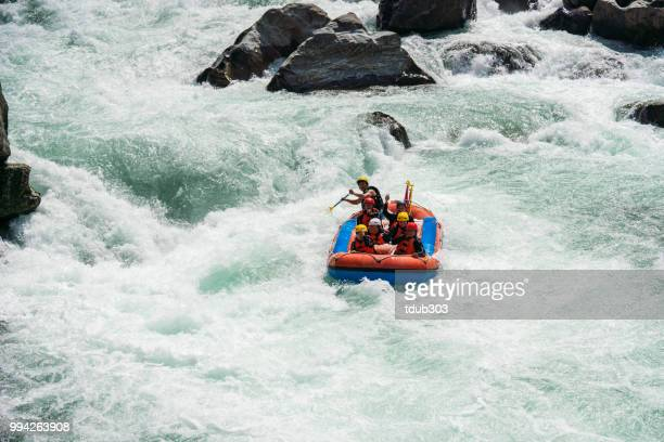small group of men and women white water river rafting - rafting stock pictures, royalty-free photos & images