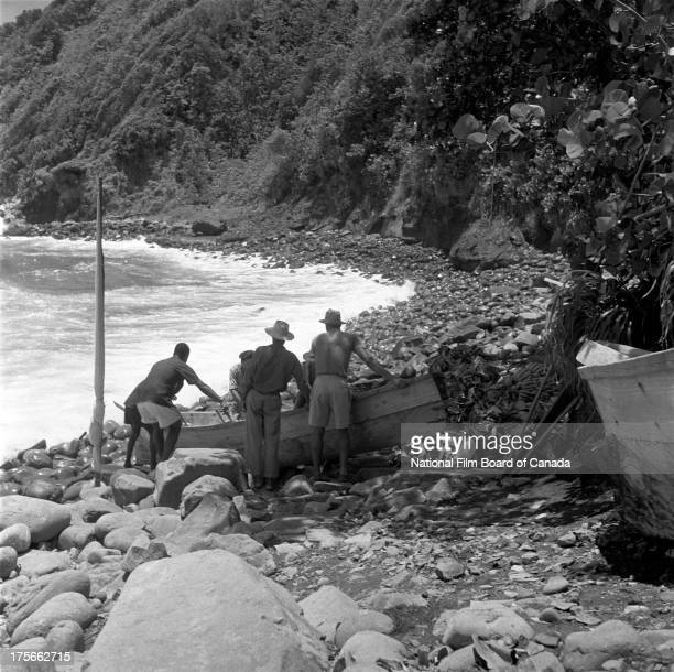 A small group of native villagers get ready to launch into the sea a dugout canoe loaded with freshly harvested bananas Dominica August 1956 Photo...