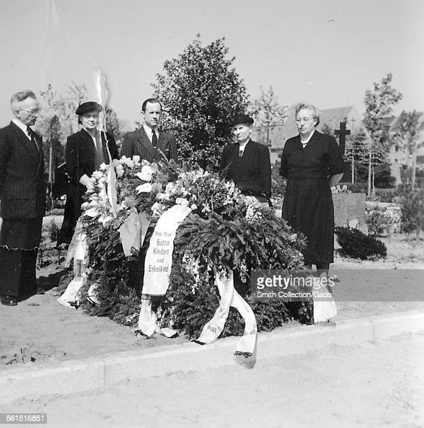 A small group of people at a cemetery beside a coffin covered in flowers and foliage Germany 1950