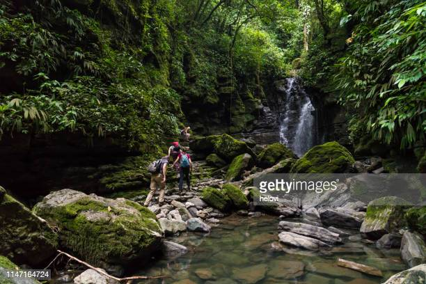 small group of people at the waterfall - ecuador stock pictures, royalty-free photos & images