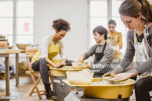 small group of people creating pottery on the wheel - ceramic stock photos and pictures