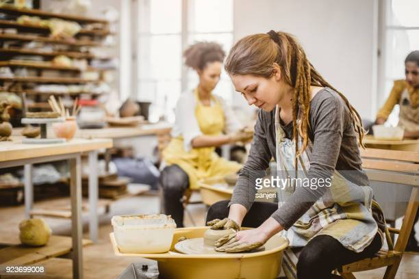 small group of people doing pottery in an art studio - pottery stock pictures, royalty-free photos & images
