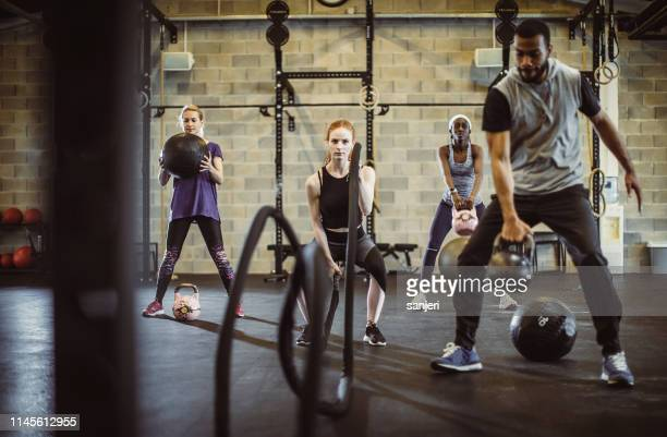 small group of people exercising in a gym - small group of people stock pictures, royalty-free photos & images