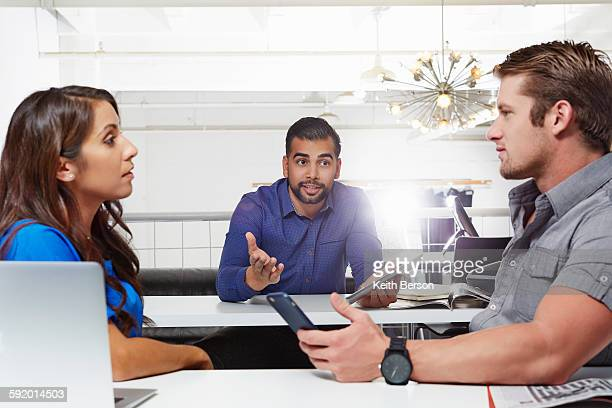 Small group of people having business meeting, male and female colleagues having disagreement