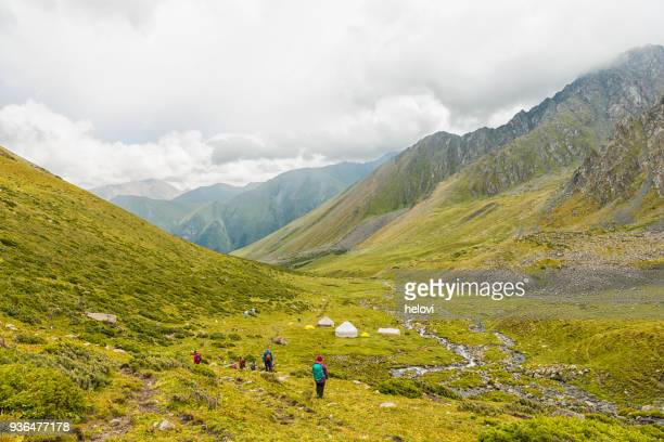 small group of people hiking into the mountain valley - kyrgyzstan stock photos and pictures