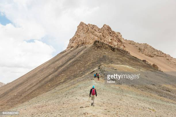 Small group of people hiking up the mountain peak