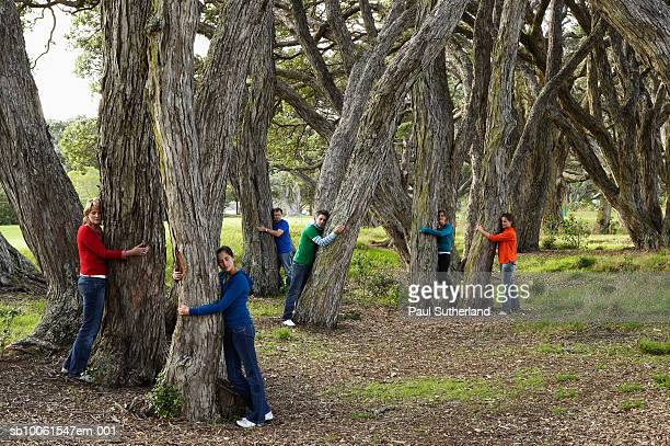Small group of people hugging trees in park
