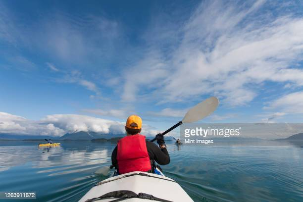 a small group of people kayaks in pristine waters of an inlet on the alaska coastline. - sea kayaking stock pictures, royalty-free photos & images