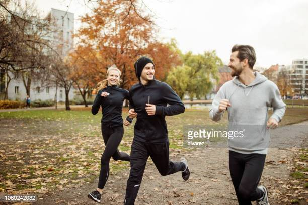 small group of people running in park - three people stock pictures, royalty-free photos & images