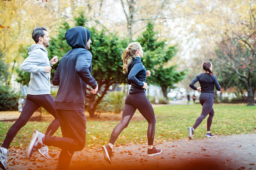 Small group of people running in the autumn park 1080232360