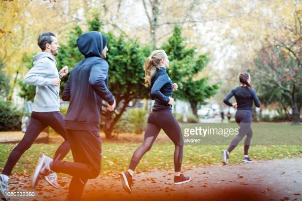 small group of people running in the autumn park - running stock pictures, royalty-free photos & images