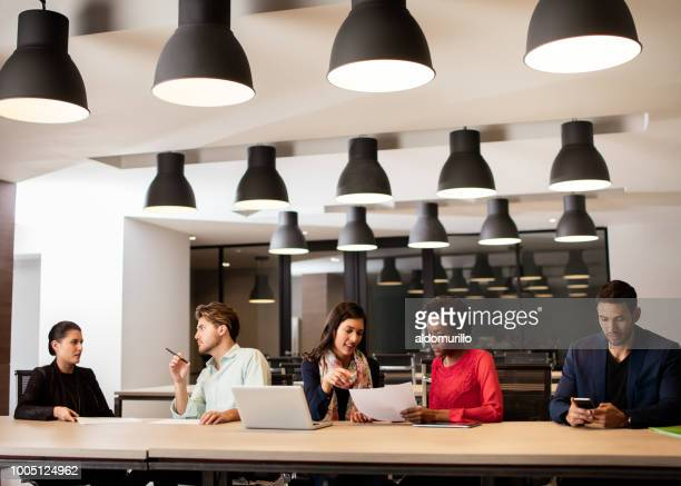 petit groupe de gens assis côte à côte dans le grand bureau - plan moyen angle de prise de vue photos et images de collection