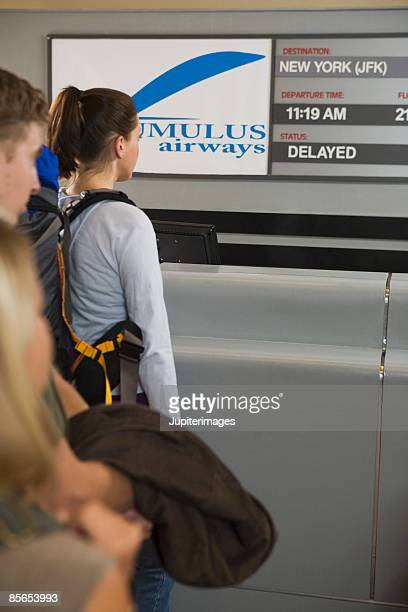 Small group of people standing in line at airport counter