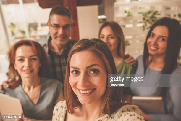 small group of people taking a selfie at work together - employee engagement stock pictures, royalty-free photos & images