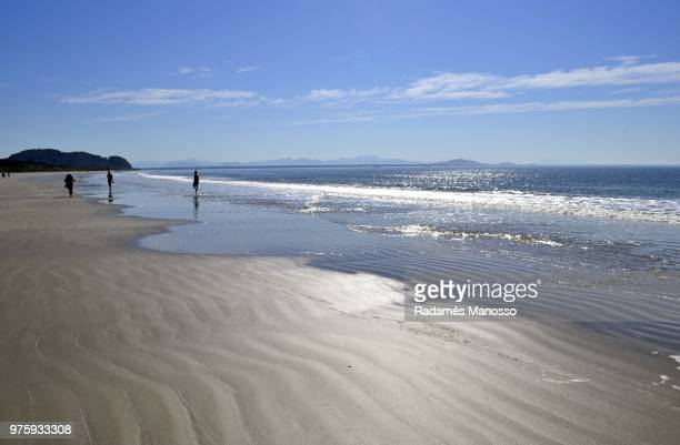 Small group of people walking on beach on sunny day, Pontal do Parana, Parana, Brazil