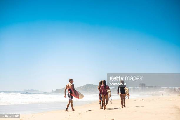 Small group of people walking on the beach with their surfboards