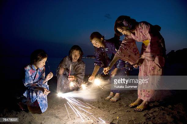 A small group of people with sparklers at the beach